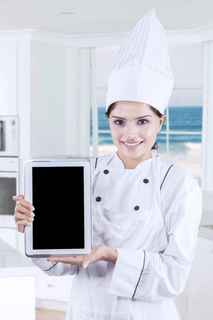 beach window: Picture of female gourmet showing empty tablet screen in the kitchen with beach background on the window