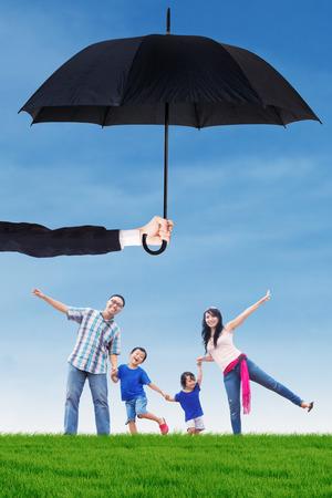 Afbeelding van gelukkig gezin met plezier op de weide onder paraplu. Leven en familie verzekeringsconcept