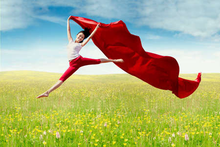 flower fields: Attractive young woman enjoy holiday while jumping on the meadow with red fabric at springtime