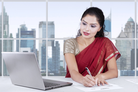 charming woman: Image of pretty indian woman working with laptop and writing document in the office while wearing traditional clothes Stock Photo
