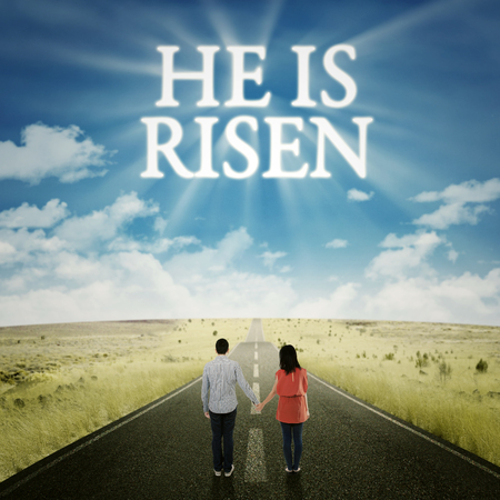 christ is risen easter: Happy couple standing on the road while holding hands and looking at text he is risen on the sky