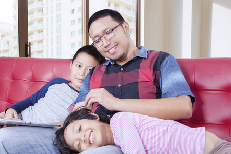 spoiling: Portrait of a young father spoiling his children while sitting on the sofa in the apartment Stock Photo