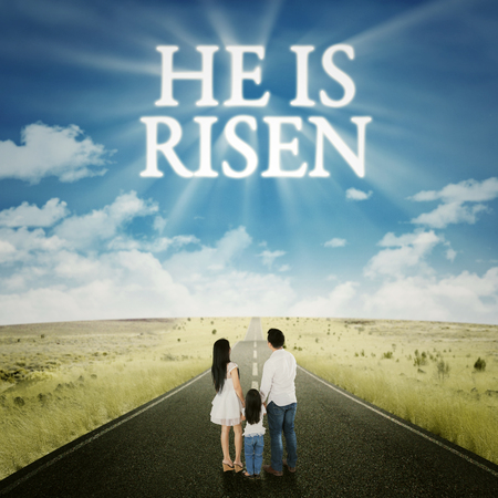 christ is risen easter: Rear view of happy family standing on the road with text he is risen on the sky