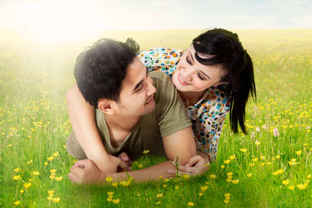 couple nature: Picture of cheerful couple lying together on the grass and smiling happy, shot in the springtime