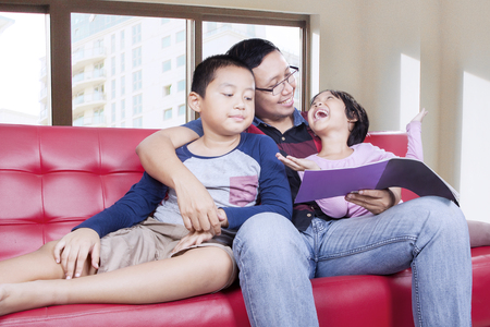 father teaching daughter: Portrait of two happy children reading a book with their father on the sofa, shot at home