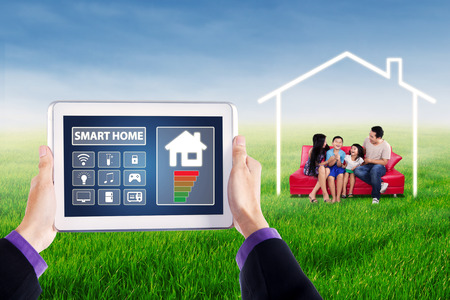 green fields: Hands holding smart home controller on the digital tablet, shot with happy family sitting on the sofa at field