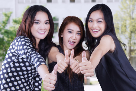 school yard: Group of three female high school students showing thumb up at the school yard Stock Photo