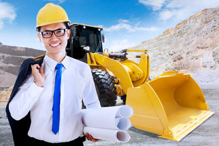 heavy equipment operator: Portrait of successful young foreman smiling at the camera with blueprint and backhoe on the construction site
