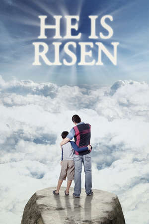 christ is risen easter: Image of young father standing on the cliff with his son and looking at text he is risen on the sky