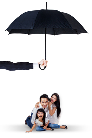 Image of cheerful family playing together in the studio under umbrella. Life and family insurance concept Stock Photo