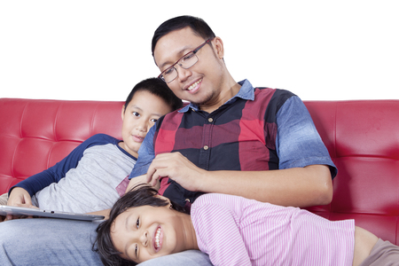 caress: Portrait of Asian father caress his daughter while sitting on the sofa, isolated on white background Stock Photo