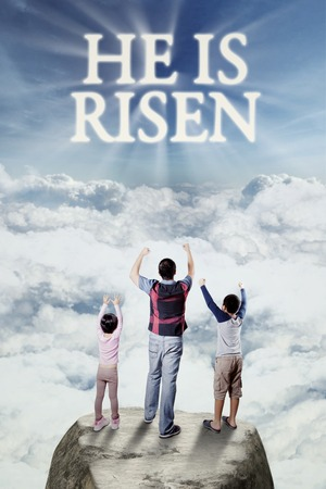 he: Cheerful father and his children standing on the cliff while raising hands and looking at text he is risen on the sky