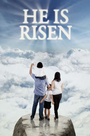 he: Back view of little happy family standing on the cliff while looking at text he is risen on the sky