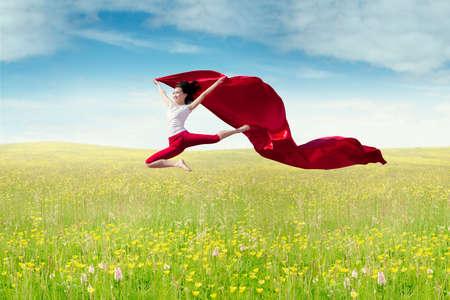 donna che balla: Bella donna giovane azienda tessuto rosso e saltando sul prato in primavera