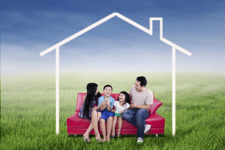 family sofa: Picture of happy family sitting on the sofa while having fun together under a dream house on the meadow