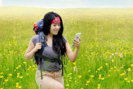 using phone: Pretty young woman walking on the meadow with hiking bag and using mobile phone as the navigation Stock Photo