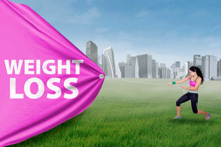 strong women: Indian young woman pulls a big flag with weight loss text at field while wearing sportswear Stock Photo