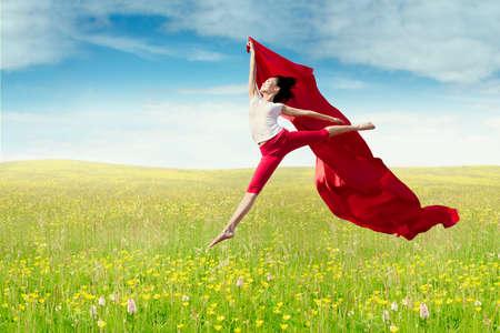 campo de flores: modelo de mujer hermosa disfruta de la libertad y saltos en el prado, mientras sostiene una tela roja