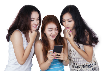 asia people: Picture of three teenage girls using a smartphone to open social media and reading message together in the studio
