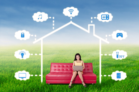 temperature controller: Pretty young woman sitting on the sofa while controlling a smart house technology system with a laptop computer, shot outdoors Stock Photo