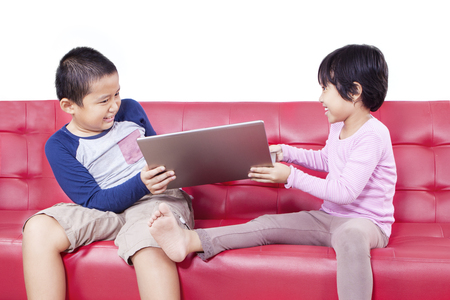 sibling rivalry: Portrait of little boy and his sister fighting over a laptop on the couch, isolated on white background Stock Photo