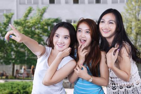 school yard: Portrait of three beautiful female high school students looking at something in the school yard