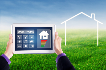 temperature controller: Image of hands holding a digital tablet with applications of smart home controller on the screen, shot at field