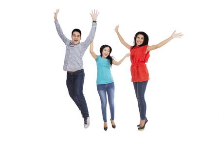 people jumping: Grupo de tres personas alegres saltando juntos en el estudio, aislado en fondo blanco