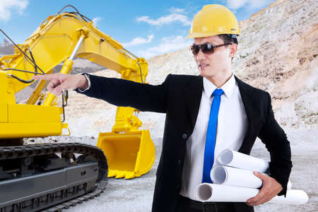 heavy equipment operator: Portrait of young foreman holding blueprint and working in the construction site with excavator on the back