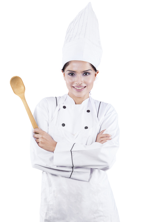 asian cook: Picture of young female chef standing in the studio with confident pose and holding a spoon