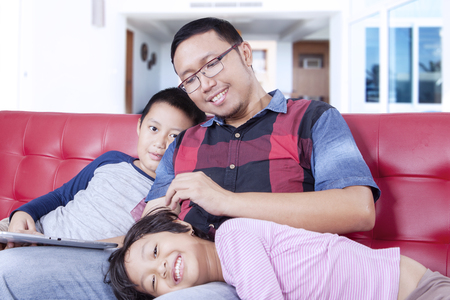 spoiling: Portrait of a young father sitting on the sofa while spoiling his children at home