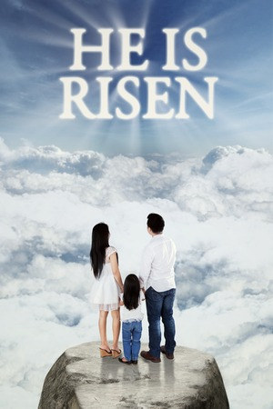 christ is risen easter: Image of two young parents and their daughter standing on the rock and looking at text he is risen on the sky Stock Photo