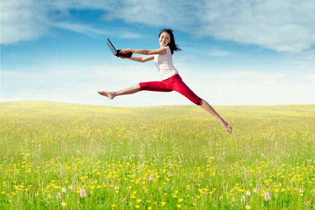 woman jumping: Beautiful young woman jumping on the meadow while holding a laptop computer at springtime