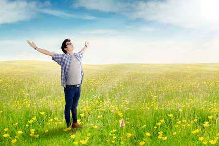 hands raised: Portrait of a young Asian man standing on the meadow with green grass, shot in the springtime