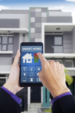temperature controller: Close up of male hand holding a smartphone and touching smart home applications on the screen Stock Photo
