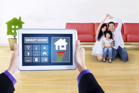 screen shot: Picture of hands holding a digital tablet with applications of smart house controller on the screen. Shot with cheerful family making a house symbol at home Stock Photo