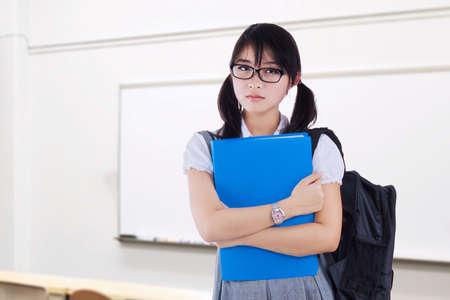 carpeta: Imagen de una hermosa estudiante femenina de pie en el aula, mientras que con mochila y la carpeta