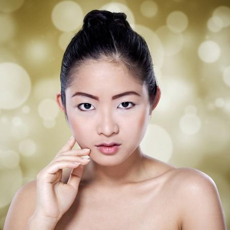 cabeza femenina: hermosa joven con la piel limpia y fresca mirando a la cámara contra el fondo del bokeh