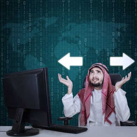 two arrows: Arabian businessman sitting in the office and looks confused with two arrows on the background Stock Photo