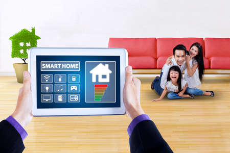 screen shot: Image of male hands holding a tablet with applications of smart house technology on the screen. Shot with Asian family playing at home Stock Photo