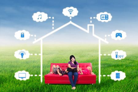 niños sentados: Madre feliz sentado en el sofá con sus niños que juegan dispositivo en fase de diseño inteligente en la casa de campo