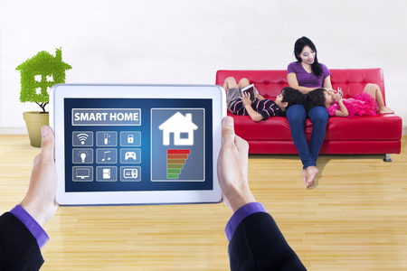 screen shot: Picture of smart house controller applications on the digital tablet screen. Shot with young mother sitting on sofa with her children at home Stock Photo