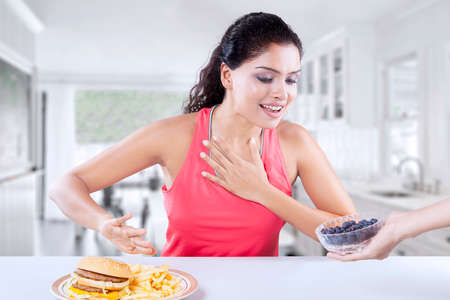avoid: Picture of beautiful Indian model refuses unhealthy cheeseburger and choose a bowl of healthy blueberry in the kitchen