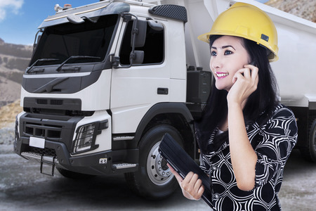 construction project: Portrait of young female engineer in builder helmet talking by phone near a big truck Stock Photo