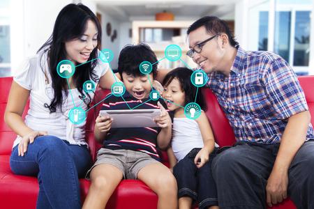Beeld van het vrolijke Aziatische familie met behulp van digitale tablet computer met smart home toepassingen in huis