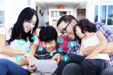 Gelukkig Aziatische familie zitten op de bank tijdens het gebruik van een digitale tablet met smart home-systeem controller