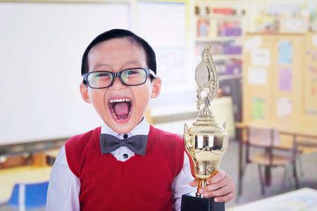 niños riendose: Niño pequeño emocionado sosteniendo el trofeo en la biblioteca Foto de archivo