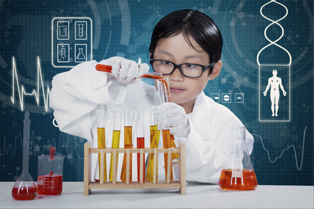science lesson: Male elementary school student doing research with chemical fluid in the laboratory