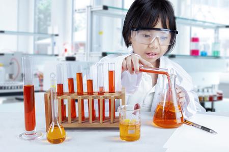 experimento: La pequeña colegiala en la lección de química, haciendo experimento químico en el tubo de ensayo, un disparo en el laboratorio
