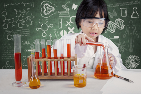 Portrait of little chemist doing experiment for healthcare with chemical fluid in the laboratory